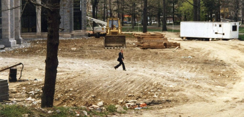 A small man walking along a huge dirt pile in a construction site