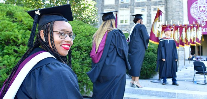 A woman graduate looks back over her shoulder at the camera.