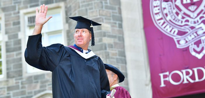 A male graduate waves from Keating Terrace