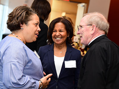 Valerie Rainford (left) with Patricia David, GABELLI '81, and Father McShane at Fordham's annual Women's Summit on October 23, 2019. Photo by Chris Taggart