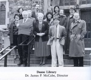 A black-and-white group photo of 13 people standing on the steps of a building