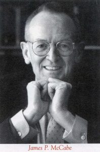 A black and white portrait of a man wearing glasses and propping his chin up with his hands