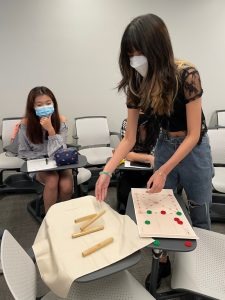 Two students wearing masks look at a pile of sticks (a board game) on a classroom desk.