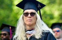 A woman with white blonde hair, sunglasses, and a graduation gown looks past the camera.