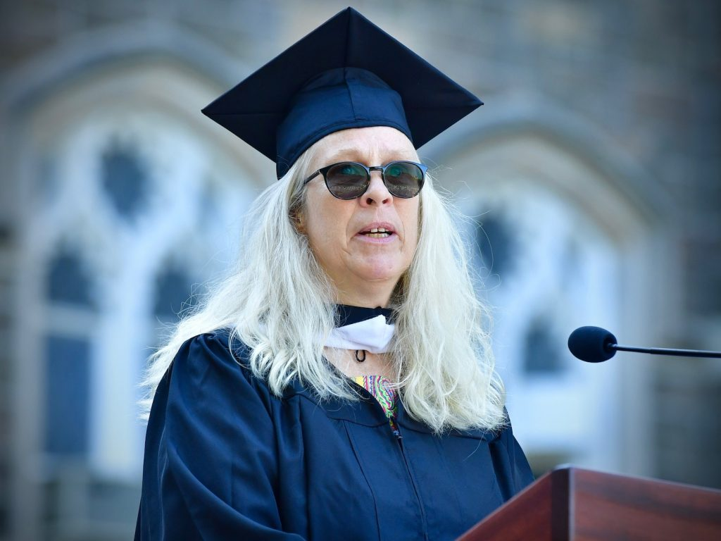 A woman with white blonde hair, sunglasses, and a graduation gown speaks at a wooden podium.