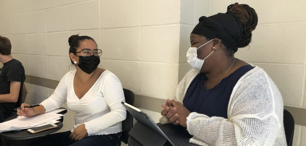 Two students wearing masks smile at each other in a classroom.