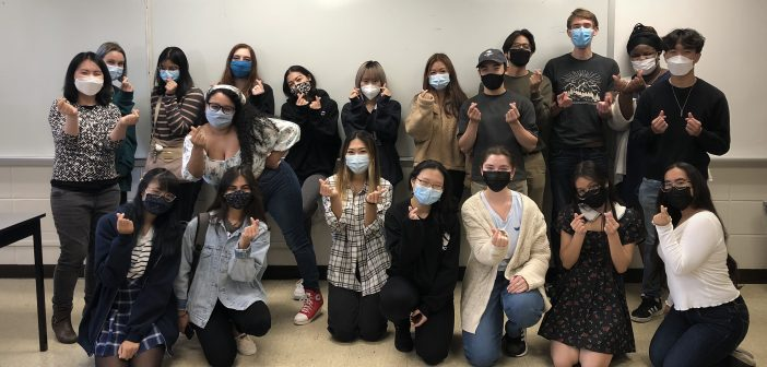 Twenty people wearing masks smile at the camera in front of a blank dry erase board and pose with their fingers in the shape of a heart.