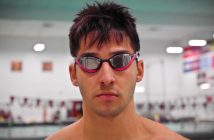 A man wearing goggles sternly looks at the camera in front of a swimming pool.