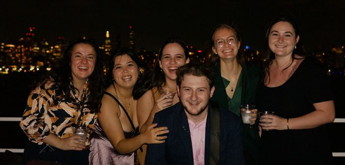 A group of recent Fordham graduates on the Young Alumni Yacht Cruise, October 2021, with the Manhattan skyline in the background