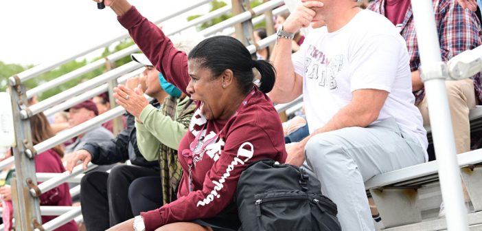 A mom cheers on her son playing football